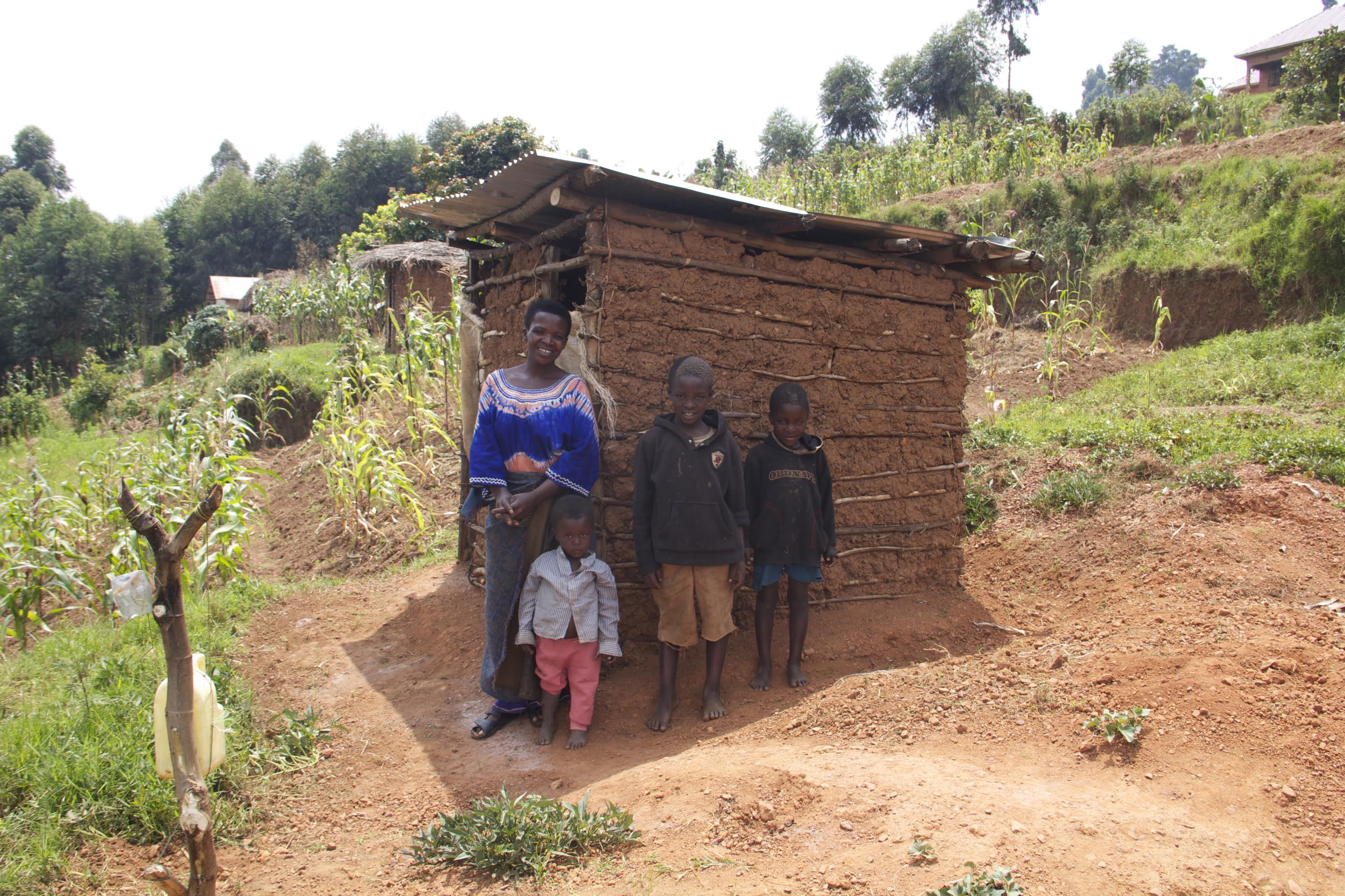 Justine and her family in Uganda with their local latrine